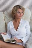 Mooi sexy blondemeisje die een boek lezen die liggen stock fotografie