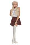 Mooi sexy blondemeisje in geruite korte rok met hoofdtelefoons royalty-vrije stock foto