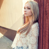 Mooi blondemeisje met lang haar in wit guipurejasje die zich dichtbij een omheining in een zonnige de zomerdag bevinden Stock Foto