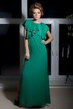 Mooi sexy elegant meisje met lange benen in een lange groene avondjurk met avondkapsel en heldere samenstelling, nieuw jaar eveni Stock Foto
