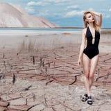 Mooi sexy leuk meisje in de spruit van de zwempakmanier in woestijn met droge gebarsten grond onder bergen als achtergrond royalty-vrije stock fotografie