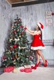 Mooi sexy meisje dat de kleren van de Kerstman draagt Jonge vrouw die Kerstboom met rode ballen thuis verfraaien Royalty-vrije Stock Afbeeldingen