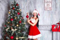 Mooi sexy meisje dat de kleren van de Kerstman draagt Jonge vrouw die Kerstboom met rode ballen verfraaien Stock Afbeelding