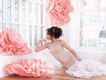 Mooi sexy meisje in een lange kleding met reusachtige roze bloemen die door het venster zitten Royalty-vrije Stock Foto's