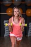Mooi, sexy meisje met domoren Actieve, jonge sportenvrouw op een vage gymnastiekachtergrond Het concept van de geschiktheidsleven Stock Foto's
