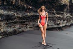 Mooi sexy meisje met grote borsten in een rood zwempak die op zwart zandstrand zonnebaden stock foto's