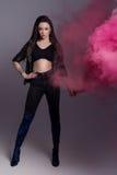 Mooi sexy modieus meisje in zwarte kleren in een koel schot in de studio met gekleurde roze rook royalty-vrije stock fotografie