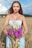 Mooi sexy slank meisje in een blauwe kleding op het gebied met een boeket van bloemen en korenaren in zijn handen bij zonsonderga Royalty-vrije Stock Afbeelding
