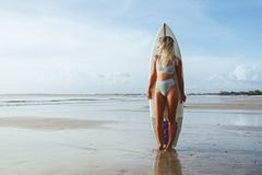 Mooi sexy surfermeisje op het strand bij zonsondergang stock foto's