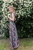Mooi sexy teder blondemeisje in een lange kleding met avondkapsel die zich in de tuin dichtbij een bloeiende aromatische boom bev Royalty-vrije Stock Foto