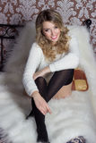 Mooi vrolijk leuk meisje met een heldere glimlach sneeuwwitte zitting in een warme sweater en sokken in bed Stock Foto's