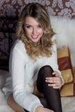 Mooi vrolijk leuk meisje met een heldere glimlach sneeuwwitte zitting in een warme sweater en sokken in bed Royalty-vrije Stock Foto's