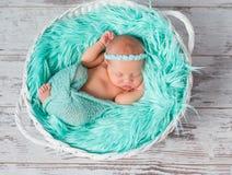 Mooi slaap pasgeboren meisje in ronde wieg met turkooise deken Stock Afbeeldingen