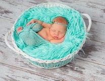 Mooi slaap pasgeboren meisje in ronde wieg met turkooise deken Stock Afbeelding