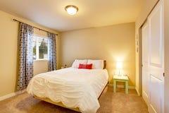 Mooi slaapkamerbinnenland met beige muren en aardige gordijnen Stock Foto's