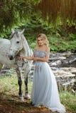 Mooi slank blond meisje die in kleding een grijs paard koesteren, outd royalty-vrije stock afbeeldingen
