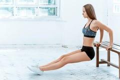 Mooi slank brunette die wat duw UPS doen bij de gymnastiek royalty-vrije stock fotografie