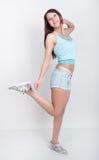 Mooi slank meisje in denimborrels en gekleurde tennisschoenen en korte t-shirt Stock Afbeeldingen