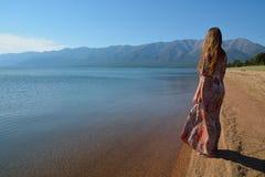 Mooi, slank meisje die zich op de kust van Meer Baikal bevinden en Stock Fotografie