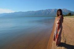 Mooi, slank meisje in een lange kleding die zich op de kust bevinden van Stock Afbeelding