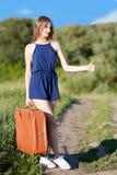 Mooi slank meisje met een koffer over gestemd auto-einde bij de weg Stock Fotografie