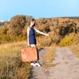 Mooi slank meisje met een koffer over gestemd auto-einde bij de weg, Stock Fotografie