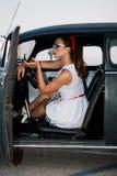 Mooi speld-omhooggaand meisje binnen uitstekende auto Stock Fotografie
