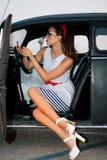 Mooi speld-omhooggaand meisje binnen uitstekende auto het letten op spiegel Stock Foto