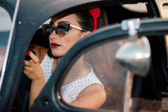 Mooi speld-omhooggaand meisje die binnen uitstekende auto make-up zetten Royalty-vrije Stock Foto