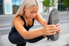 Mooi Stedelijk Wijfje die Haar Been uitrekken vóór Oefening stock fotografie