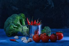 Mooi stilleven in rustig Broccoli, knoflook en rode tomaten Spaanse peperpeper in een kleine emmer ongebruikelijk licht Royalty-vrije Stock Fotografie