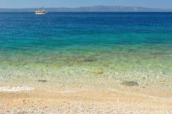 Mooi strand met duidelijk water in voorzijde en schip en eiland Hvar op achtergrond royalty-vrije stock foto
