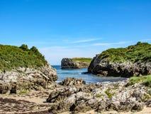 Mooi strand Playa DE Buelna met blauw oceaanwater, rotsachtige die klippen met groene vegetatie en blauwe hemelachtergrond worden stock foto's