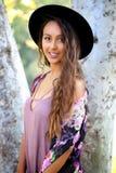 Mooi tan meisje in een zwarte hoed door een boom stock foto