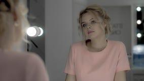 Mooi teder meisje die in roze kleding de spiegel in make-upruimte bekijken royalty-vrije stock foto