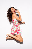 Mooi Tiener Modelbrunette-meisje die in witte kleding op witte achtergrond met rode lolly springen binnen Vrije gelukkige vrouw Royalty-vrije Stock Afbeelding