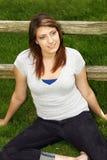 Mooi tienermeisje dat buiten door omheining glimlacht Stock Afbeeldingen
