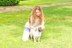 Mooi tienermeisje die een pug hond in openlucht in een park voeden royalty-vrije stock afbeelding