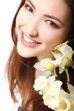 Mooi tienermeisje die en met bloemnarcissen glimlachen en lookin Stock Fotografie