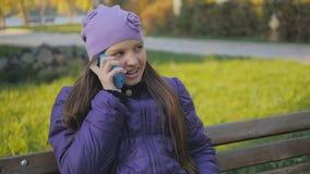 Mooi tienermeisje die en op de telefoon in de herfstpark glimlachen spreken Tand steunen Slow-motion stock video