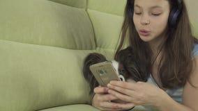 Mooi tienermeisje in hoofdtelefoons die karaokeliederen in smartphone met de lengtevideo van de hondvoorraad zingen stock video