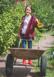 Mooi tienermeisje in wellies die in tuin werken Stock Foto