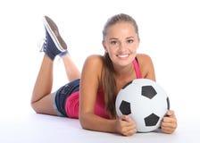 Mooi tienervoetbalmeisje dat op vloer ligt Stock Foto