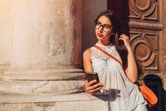 Mooi toeristenmeisje die slimme telefoon in openlucht met behulp van De vrouw die van het Middenoosten naar juiste manier met nav royalty-vrije stock fotografie