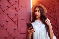 Mooi toeristenmeisje die telefoon in openlucht met behulp van De vrouw die van het Middenoosten naar juiste manier met navigator  royalty-vrije stock afbeelding