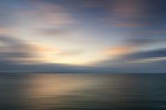 Mooi trillend zonsopganglandschap over kalme overzees met onduidelijk beeld filt Stock Afbeeldingen