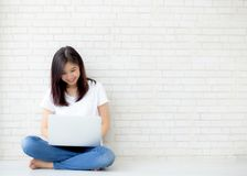 Mooi van portret Aziatische jonge vrouw die online laptop zitting werken aan het cementachtergrond van de vloerbaksteen Royalty-vrije Stock Afbeelding