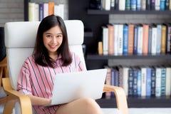 Mooi van portret Aziatische jonge vrouw het freelance werk online laptop zitting op stoel bij woonkamer Stock Fotografie