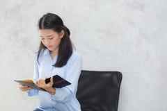 Mooi van portret bedrijfs Aziatische jonge vrouwenlezing op notitieboekje met succes op cementachtergrond Stock Foto