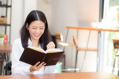 Mooi van portret bedrijfs Aziatische jonge vrouwenlezing op notitieboekje met succes op lijst Royalty-vrije Stock Foto